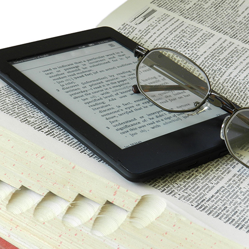 eyeglasses on top of an ereader on top of an open reference book