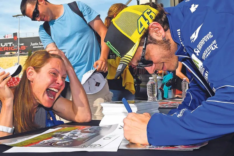 Valentino Rossi signing autographs for a fan