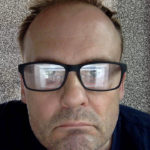 A person wearing black framed glasses that reflect a screen obscuring his eyes.