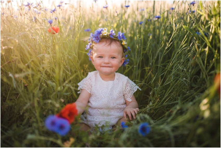 happy baby girl in the flower field