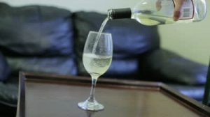 stock-footage-hand-pouring-a-bottle-of-white-wine-in-a-wine-glass-on-a-table-at-home