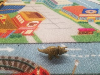 toy triceratops on road themed rug