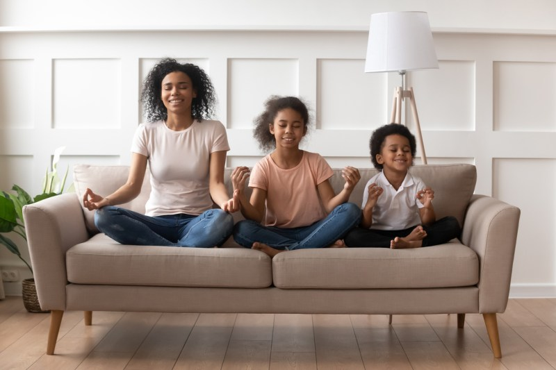Mother and two kids practicing mindfulness on a couch