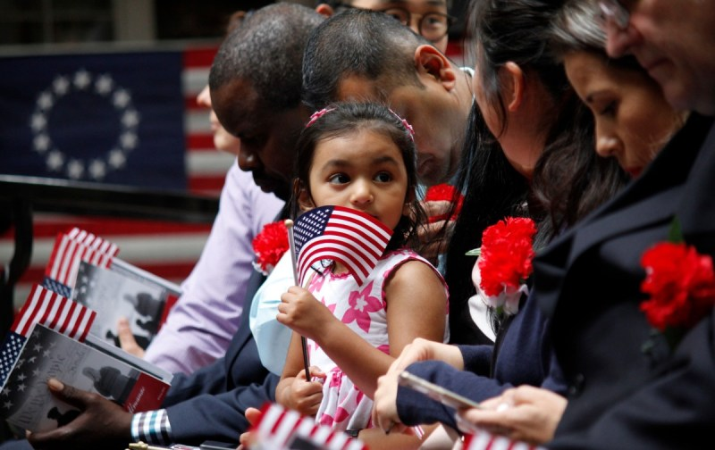 Girl holding an American flag at a naturalization ceremony