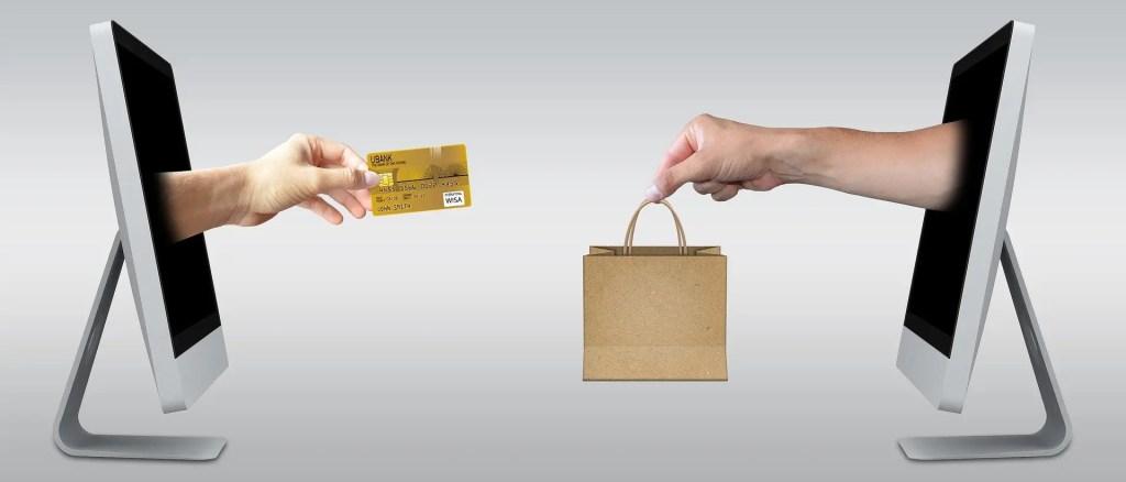 une main sortant d'un ordinateur avec une carte bleu, va vers une autre main qui tient un sac de shopping