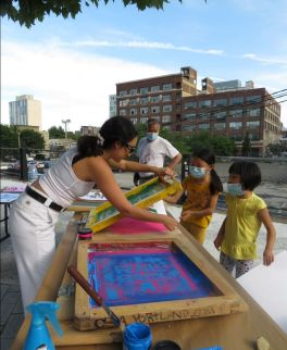 An artist assists two young girls to screen print a Rail Park design on paper