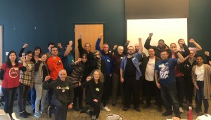 A group photo of 23 Montgomery County Branch members raising a fist in the air
