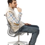 Young man sitting in chair with poor posture.