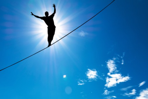 Man balancing on trapeze wire. Balance.