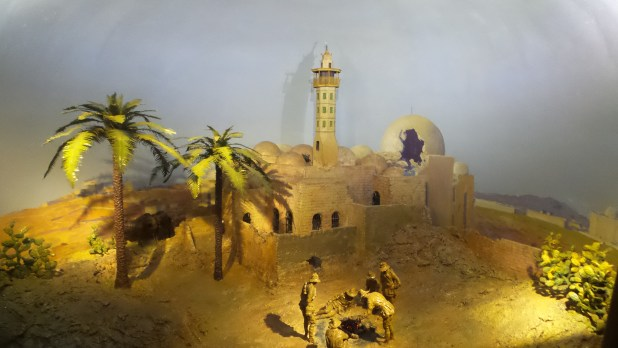 The long trek ends The diorama depicts a handful of light horsemen preparing a meal in the shadow of a battle-scarred mosque. Their mounts are tethered under a clump of palms in the background.