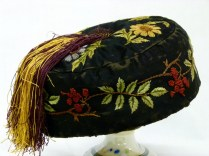 016/004 Men's ornate smoking hat. Obviously made as a costume as it has a cardboard base. Black cotton covered with embroidered flowers berries and leaves in yellow, red, green and brown. On top of crown is an ornate covered button that attaches a yellow and claret coloured silk tassle that hangs down the hat below the crown.