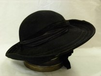 016/008 Women's hat. Black felt with medium high crown and wide brim. Brim is wider at the front than the back and has 4 rows of stitching to make it stiff, turned up and edged with black grosgrain ribbon. The hat band is black satin and black velvet ruched together at front and attached with black felt strip with a small felt bow on right hand side. There is no label but there is a wide black satin ribbon underneath attached to black hat elastic ties on each side. A large velvet bow hangs under hat on the ribbon to the left hand side.