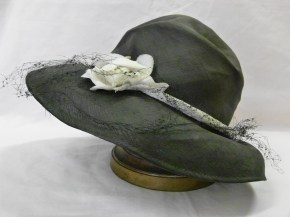Women's hat. Black straw, flat crown with very wide, flat, stiff gauze molded brim. Wire mold the hat and keeps the brim in shape, two wire claws on the side also help to keep the hat in place on the head. Hat decorated on top left with 1 black/brown organdie rose and 1 pink organdie rose with leaves attached. Pearl hat pin attached and would be needed to also help keep hat in place as it is very shallow with wide brim. No label, black silk lining in crown.