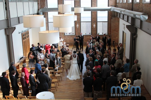 Walking down the aisle at Kitchen Chicago and city view loft wedding