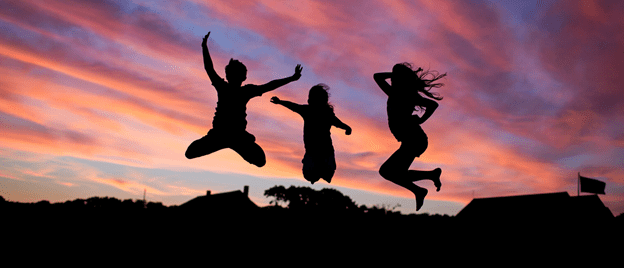 three figures jumping against dramatic sunset