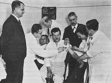 1934 photograph of malarial transfusion from one patient to a neurosyphilitic patient.  Dr. Wagner-Jauregg is in a suit on the right.