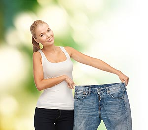 fitness, diet and good shape concept - sporty woman showing big pants