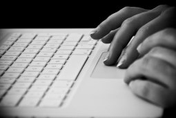 Black and white close up of hands typing on a laptop