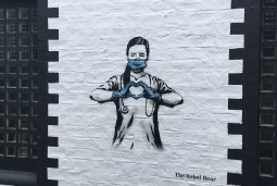 Graffiti of nurse wearing a mask and making her hands form a heart in front of her