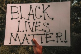 A black hand holds a Black Lives Matters sign