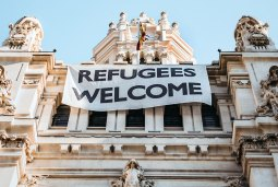 A city building with a white sign saying Refugees Welcome
