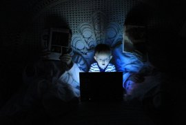 Image of a small child light up by a blue screen in bed with parents who are in the dark