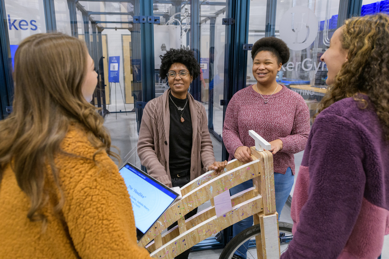 A diverse group of female Mechanical Engineering students gather around a wooden bike built for a competition.