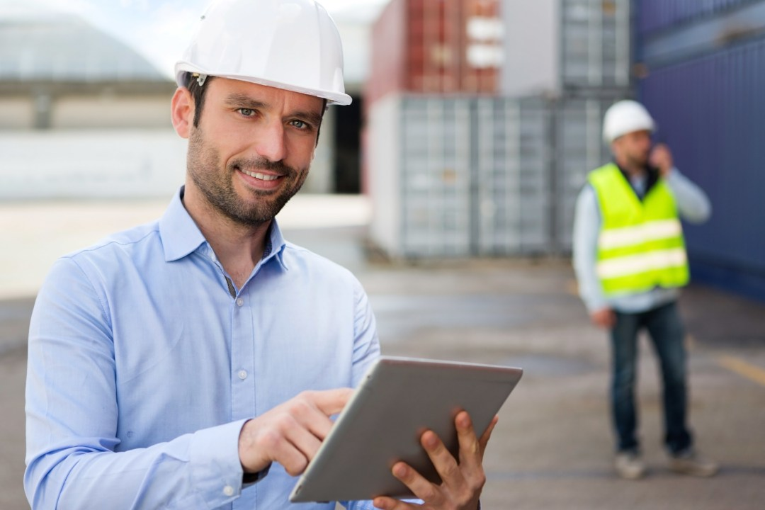 Young Attractive engineer using tablet on the dock