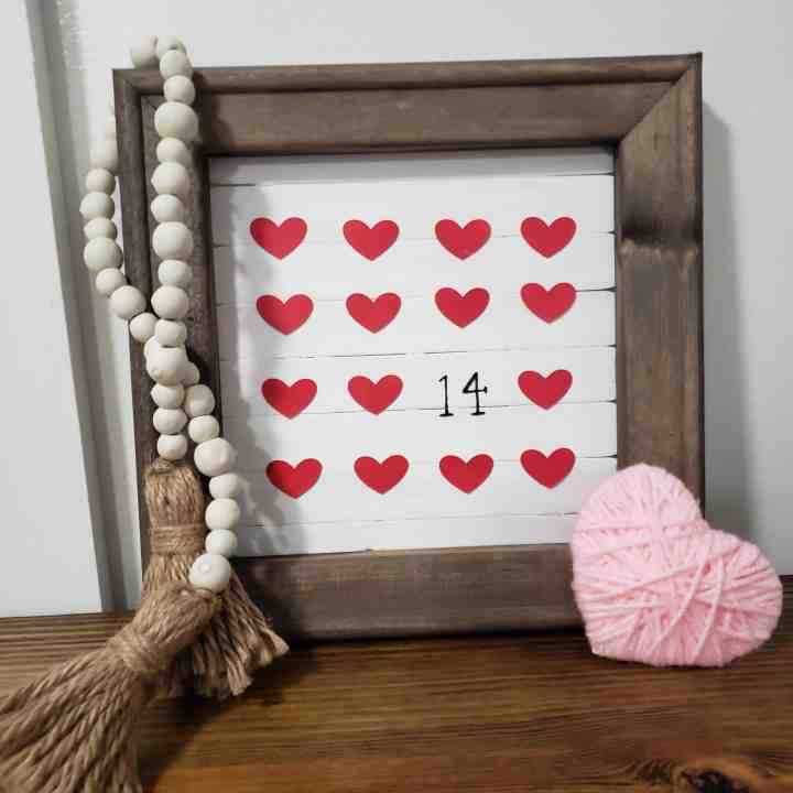 DIY Valentine's Day sign with wooden beads hanging of it and a yarn heart next to it