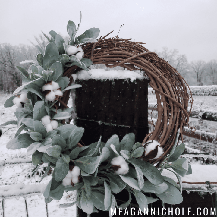 winter wreath hanging on a post with a snowy background