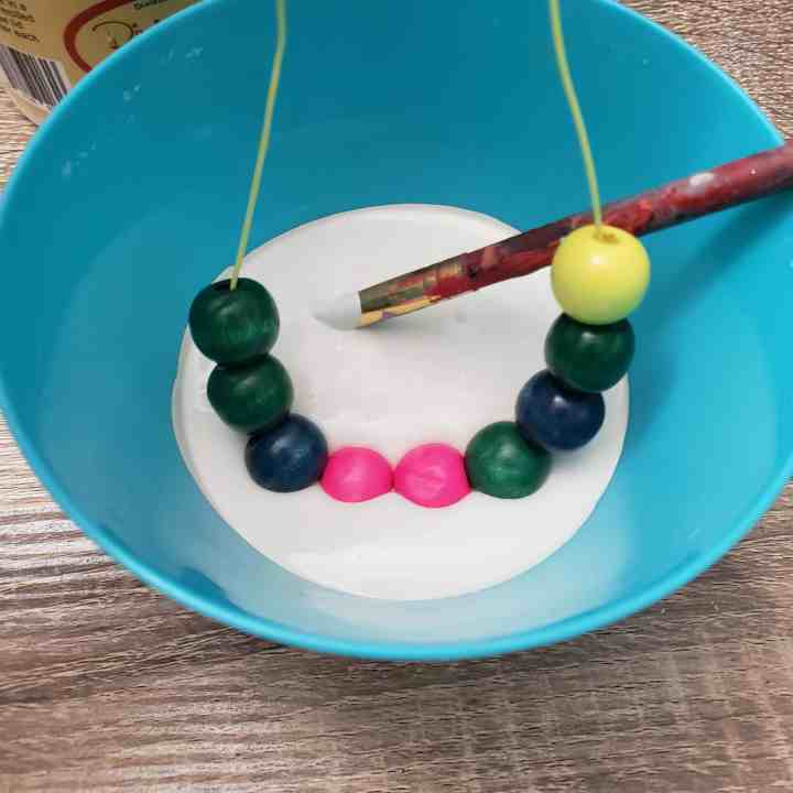 dipping beads in paint for a Farmhouse Wooden Bead Garland
