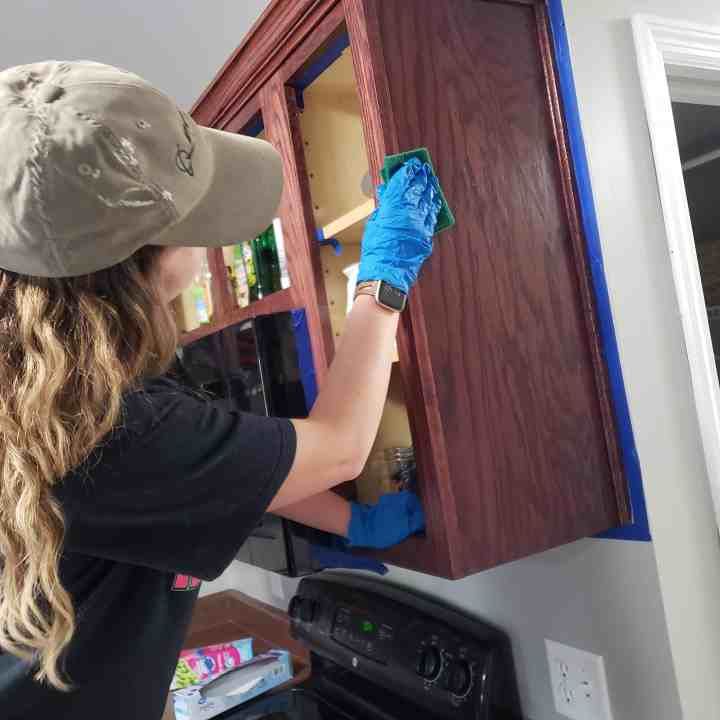 female deglossing a kitchen cabinet  for a kitchen cabinet makeover tutorial photo