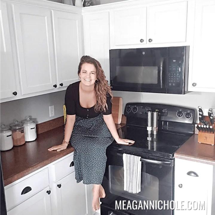 brunette female sitting in kitchen for a kitchen cabinet makeover tutorial photo