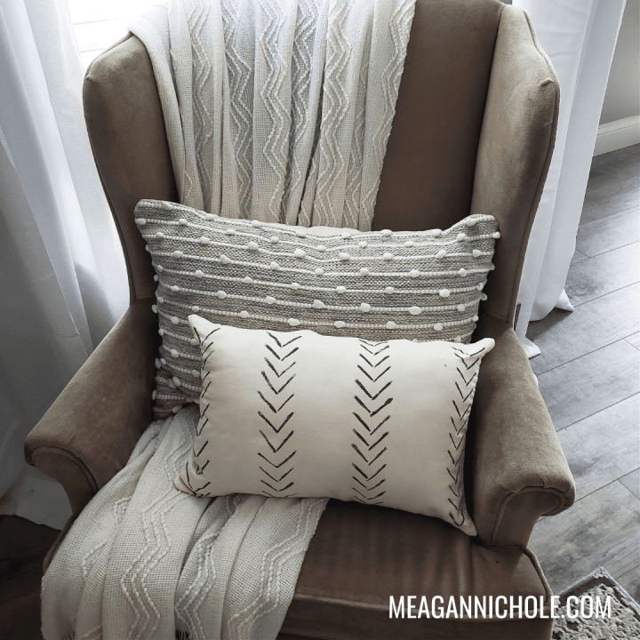 gray and white pillows on a brown chair for a how to paint pillows blog post tutorial