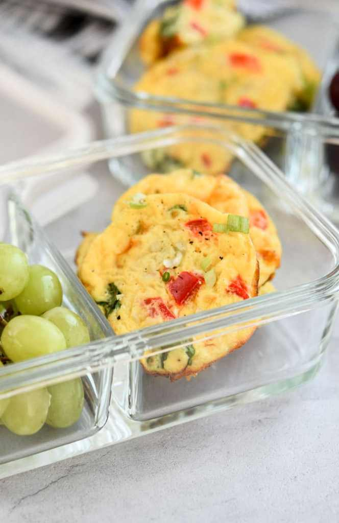 Baked Cottage Cheese Egg Muffins in meal prep container with grapes