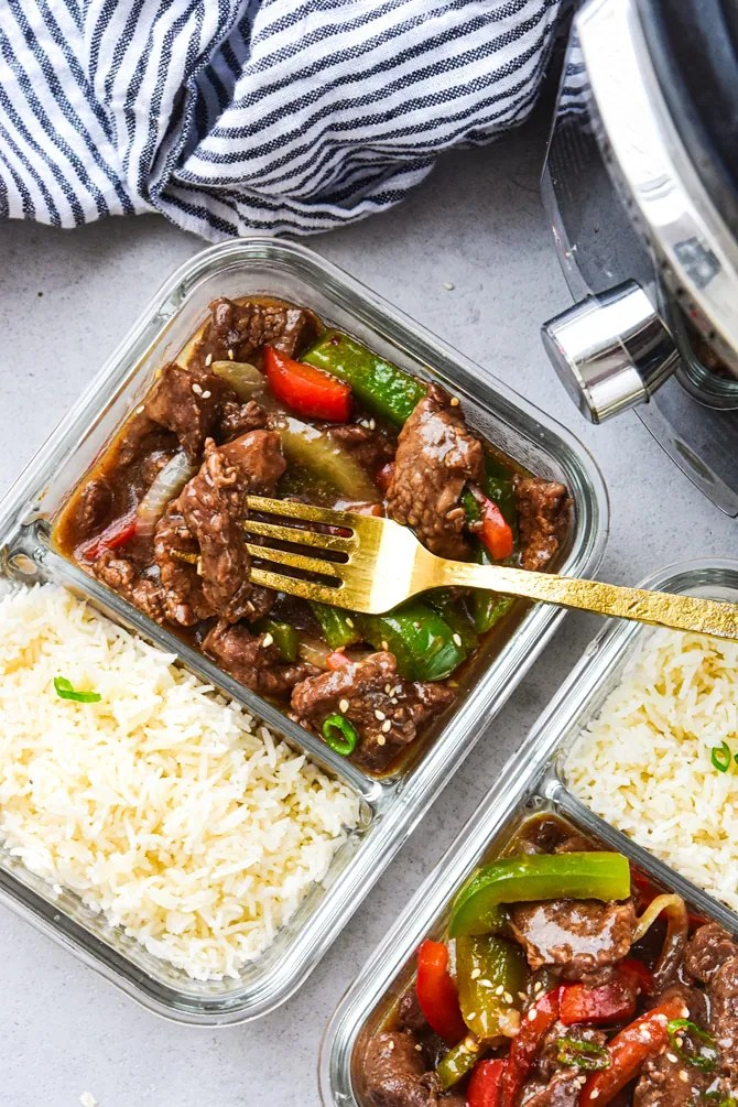 Instant Pot Pepper steak in meal prep containers with fork