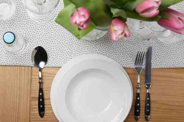 white plate, silverware set, and tulips on a wooden table