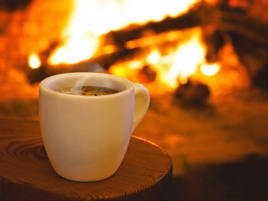 mug of steaming coffee by fireplace