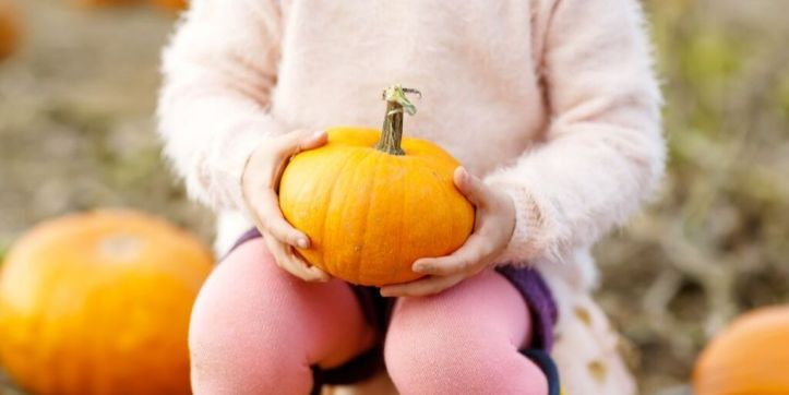 child-holding-pumpkin