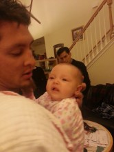 Mike holding Eva while Uncle Kevin looks on