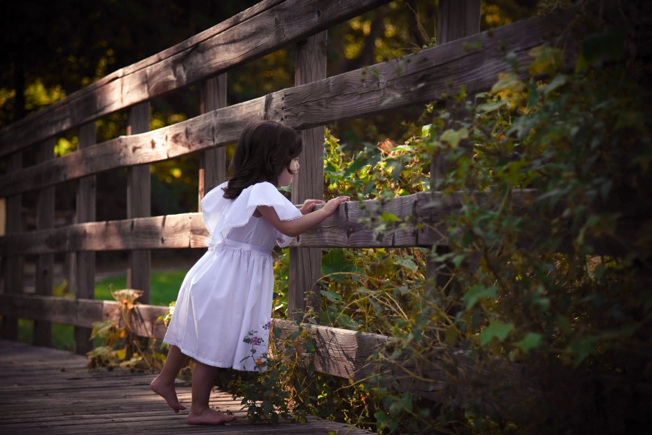 Toddler girl in white mexican dress next to wooden fence, Babs Mullinax, me and grace, me & grace, Fort Wayne photographer, photo gifts, lifestyle photography, family photos, ideas for family photos, indoor photography, fun family photographer, long-distance family