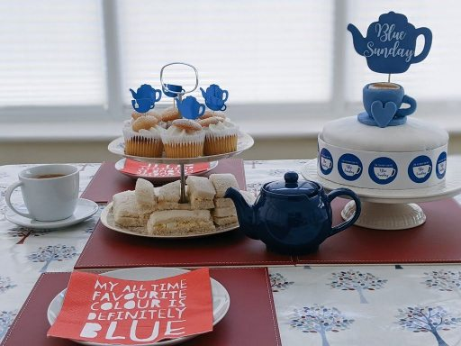 A table laid with teacup, cake stand, teapot and cake