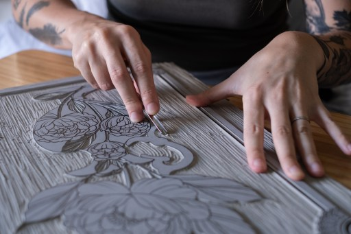A photo of a person cutting out a floral print on some lino