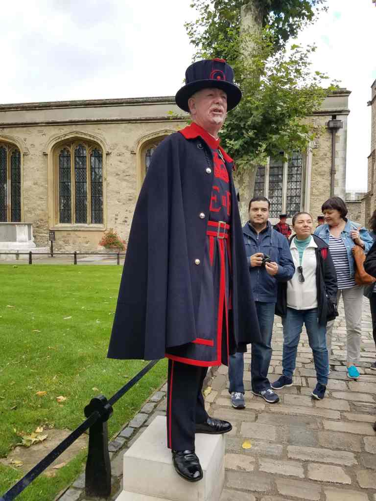 A man in navy blue and red beefeater uniform speaks to a tour group in the Tower of London