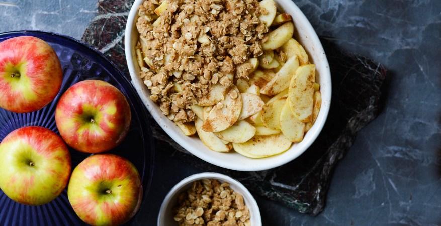 apples beside an apple crisp on a dark background