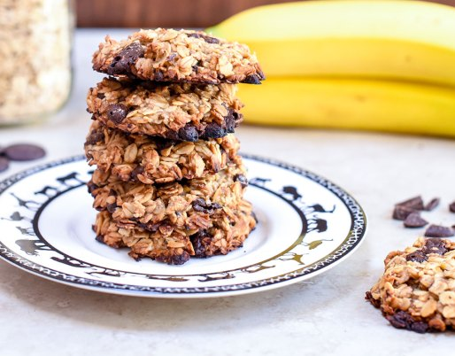 cookies stacked on plate with bananas in background