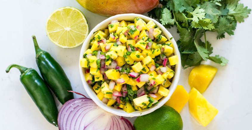 mango salsa in bowl surrounded by ingredients