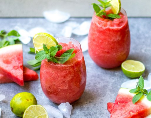 watermelon slushie in glasses with mint and lime wedges
