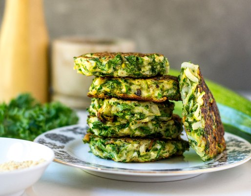 zucchini fritters stacked on plate