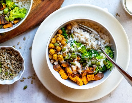 chickpea grain bowl on table with fork and seeds on the side